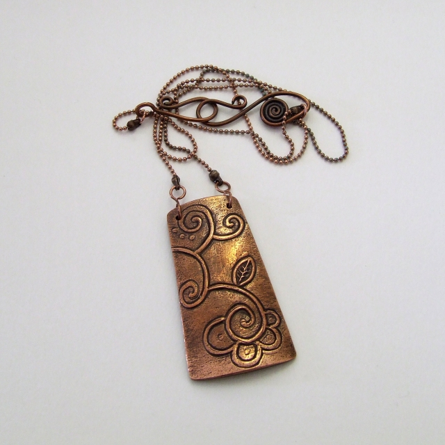 Carved copper pendant